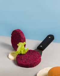beetroot burger with lettuce and mayo in a lightblue background