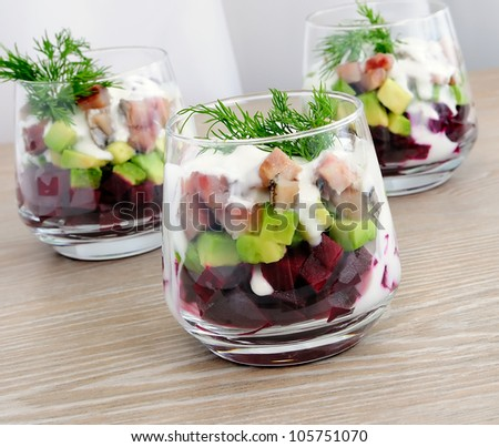 Beetroot salad with avocado and herring in cream sauce in a glass