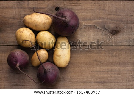 Beets and potatoes on a wooden background. Harvest season #1517408939