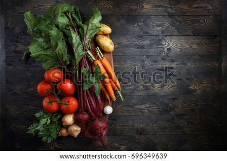 Beets, onions, garlic, carrots, potatoes, tomatoes, parsley and bay leaves on the table