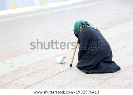 Beggar old woman asks for alms sitting on a city street. Poverty, homeless and begging concept Photo stock ©