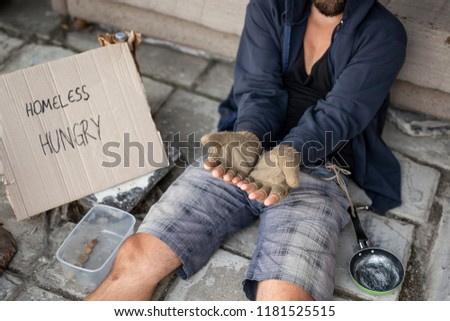 Beggar wearing hoodie over cap and fingerless gloves, sitting in the street, begging for money. Focus on the hands