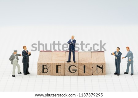 Begin, company establish or start own business concept, miniature figure businessman standing on wooden stamp building the word BEGIN on grid line note book with congratulation clapping people.