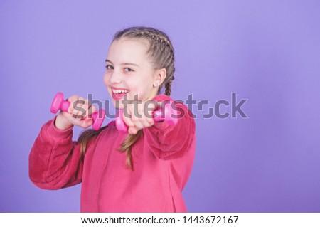 Beginner dumbbell exercises. Child hold little dumbbell violet background. Sport for teens. Easy exercises with dumbbell. Toward healthier body. Rehabilitation concept. Girl exercising with dumbbell.