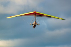 Beginner girl pilot withcolorful hang glider wing. Learning hang gliding. Extreme sports activity