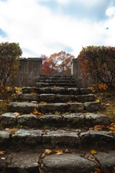 Beginning of the rustic stone stairs in focus, stone fence on the right and left sides of stairs out of focus, yellow leaves on the stairs in a chaotic order, and gloomy sky and red tree in the back