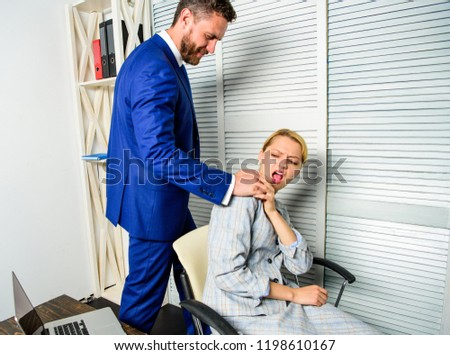 Behavior rule and subordinate at work. Boss unacceptable behavior with subordinate employee. Boss touch shoulder of female office colleague. Tired woman worker relaxing while man massaging her.