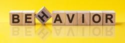 BEHAVIOR Word made of building blocks on a light yellow background, the reflection in the surface