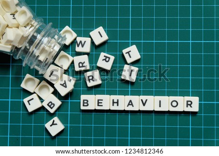 Behavior word made of square letter word on green square mat background.
