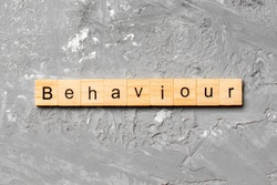 BEHAVIOUR word written on wood block. BEHAVIOUR text on cement table for your desing, concept.