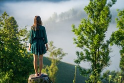 Behind a Caucasian woman standing barefoot on a tree trunk and looking into the distance at the standing green trees, reflecting on the effects of massive deforestation. Copy space.