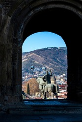 Behind a entrance of Metekhi church, King Vakhtang Gorgasali on the horse monument in  on the background of cable car and ancient old Tbilisi, Georgia.