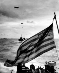 Behind an American flag, a convoy of landing craft head for Utah Beach on June 6, 1944. Each ship has barrage balloon connected by a cable during the D-Day invasion of Normandy on June 6, 1944.