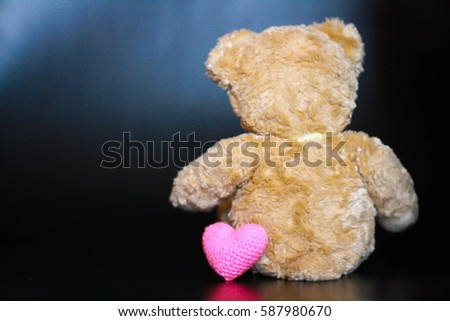 behind cute teddy bear and pink heart on black background. #587980670