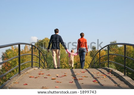 behind family with baby on autumn bridge