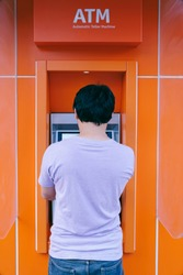 Behind of a young man using ATM Automated teller machine (Automatic banking machine) to withdraw cash money, Banking and Business Concept.
