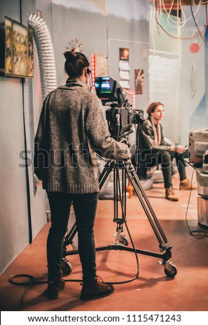 Behind the scene. Actor in front of the camera on the film set in film studio.  #1115471243