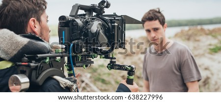 Behind the scene. Actor in front of the camera on the film set outdoor location. Group movie scene