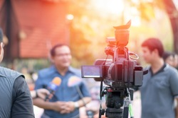 Behind the scene concept. Cameraman working on professional camera taking film interviewer interview celebrity people making news outdoors.