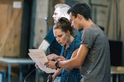Behind the scene. Director of the play rehearses the play with the actors according to the script