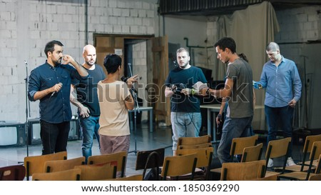 Behind the scene. Director of the play rehearses the play with the actors according to the script Сток-фото ©