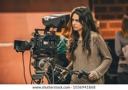Behind the scene. Female cameraman shooting the film scene with camera in film studio