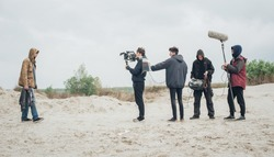 Behind the scene. Film crew team filming movie scene on outdoor location. Group cinema set