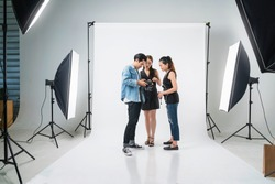behind the scene of Professional photo shooting at the studio: a beautiful young asian model is smiling and posing with makeup artist is makeup photographer is taking pictures with a digital camera