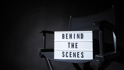 Behind the scenes letterboard text on Lightbox or Cinema Light box. Movie clapperboard and director chair. Background black color. camera shootin in video production studio.
