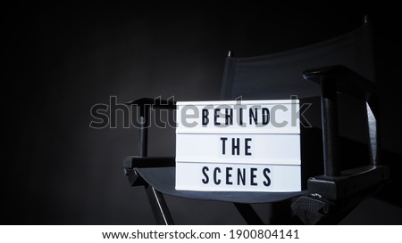 Behind the scenes letterboard text on Lightbox or Cinema Light box. Movie clapperboard and director chair. Background black color. camera shootin in video production studio. Stock photo ©