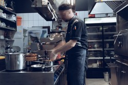 Behind the scenes of brands. The chef cooking in a professional kitchen of a restaurant meal for client or delivery. Open business from the inside. Meals during the quarantine. Hurrying up, motion.