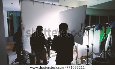 Behind the scenes of shooting video or movie production crew team and silhouette of camera and equipment in studio.