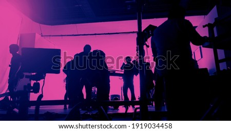 Behind the scenes of shooting video production and lighting set for filming movie which film crew team working in silhouette and professional equipment in studio for video. video production concept.