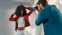 Behind the Scenes on Photo Shoot: Beautiful Black Model Posing for a Photographer, he Takes Photos with Professional Camera. Stylish Fashion Magazine Photoshoot done with Pro Equipment in a Studio