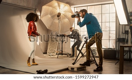 Photo of  Behind the Scenes on Photo Shoot: Beautiful Black Model Posing for a Photographer, he Takes Photos with Professional Camera. Stylish Fashion Magazine Photoshoot with Pro Equipment in a Studio