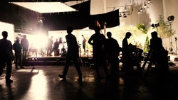 Behind the scenes or the making of film video production and movie crew team working in silhouette of camera and equipment set in studio.