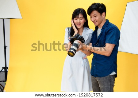 Behind the scenes, photographers are checking pictures with beautiful young women models smiling and posing in the studio with the backdrop and studio lights. Selective focus