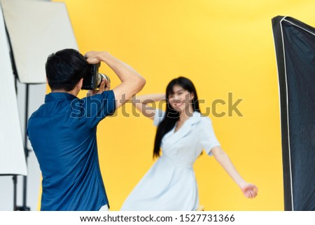 Behind the scenes, photographers are using cameras and lenses to shooting pictures of beautiful young women models smiling and posing in the studio with the backdrop and studio lights. Selective focus