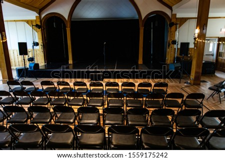 Behind view of concert hall room with empty stage and empty chairs waiting for guests to arrive
