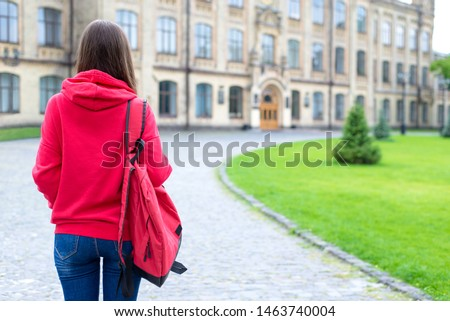 Behind view photo portrait of nervous scared stressed teen person looking at the door of her new place of studying wearing bright clothes standing near green lawn #1463740004
