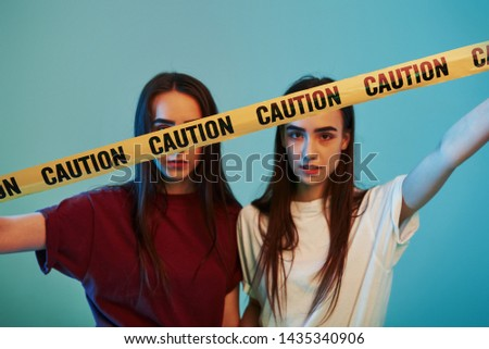 Behind yellow caution tape. Studio shot indoors with neon light. Photo of two beautiful twins.