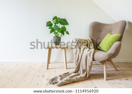 Beige armchair with a green pillow, blanket and a wooden table with a potted plant, fruit salad tree (Monstera deliciosa). Empty white wall in simple living room interior. Copy space #1114956920