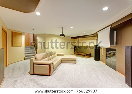 Beige basement movie room features a leather sectional under a ceiling mounted movie projector.  #766329907