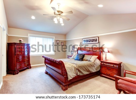 Beige bedroom with cathedral ceiling, carpet floor and great carved bed frame and storage cabinets