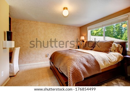 Beige bedroom with soft carpet floor. Furnished with wooden queen size bed, desk and chair