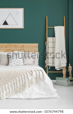 Beige blankets on bed and ladder in boho bedroom interior with poster on green wall #1076744798