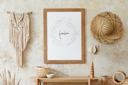 Beige boho interior of living room with mock up poster frame, elegant accessories, dried flowers in vase, wooden console and hanging macrame in stylish home decor.