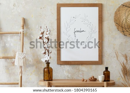Beige boho interior of living room with mock up poster frame, elegant accessories, dried flowers in vase, wooden console and hanging rattan hut in stylish home decor. Template.