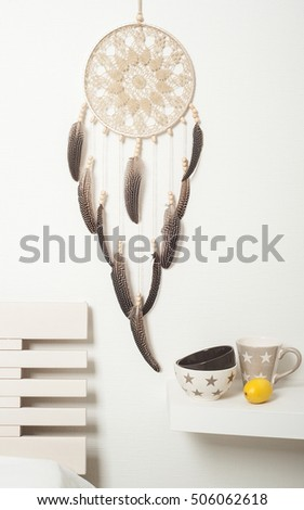 Beige brown dream catcher with feathers on white wall. Copyspace for text #506062618