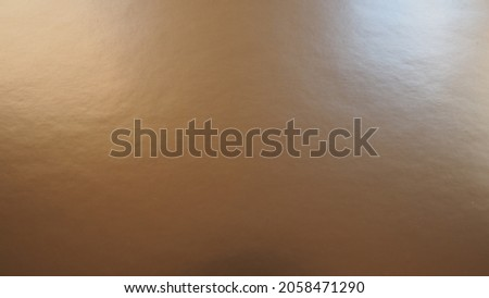 Beige - brown paper with a metallic sheen, lighting shines from both sides to the right and left. Abstract background with gradient. Copy space. Texture and bumps on the surface. The shine